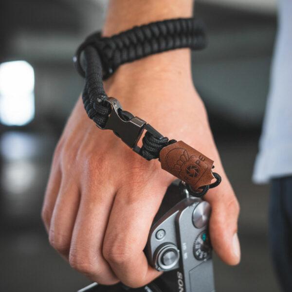 C-Rope Kamera Handschlaufe aus handgeflochtenem Paracord Seil mit Schnellverschluss in schwarz getragen als Closeup